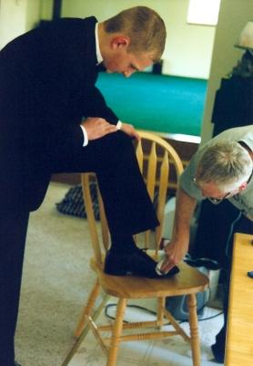 Joe polishing Jason's shoes before a formal